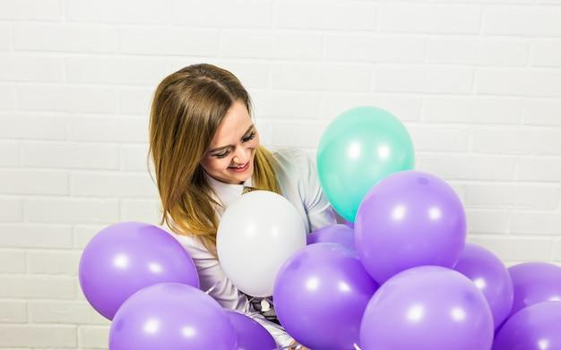 Vakantie, viering en levensstijl concept - mooie vrouw met kleurrijke ballonnen binnenshuis Premium Foto