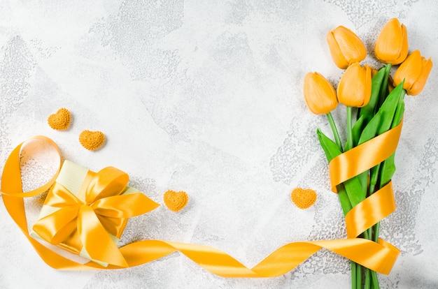 Vakantieachtergrond met tulpen en giftdoos Premium Foto