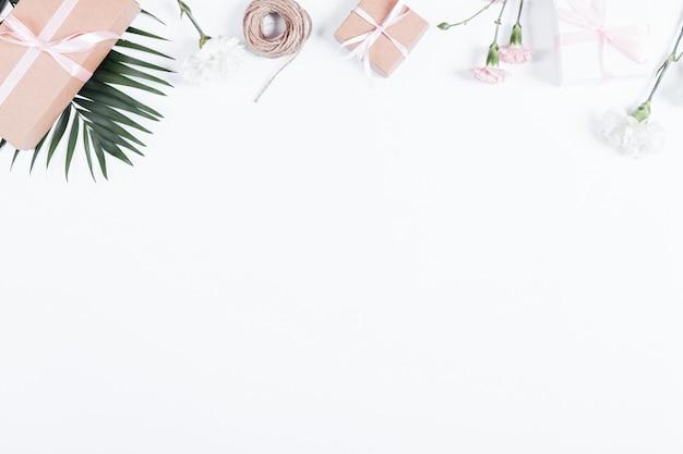 Vakken met geschenken, linten, touw en bloemen op witte tafel, bovenaanzicht Premium Foto