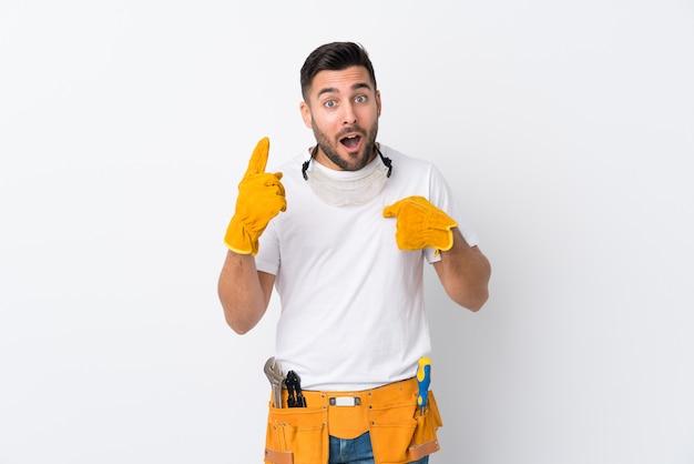 Vaklieden of elektricienmens over geïsoleerde witte muur met verrassingsgelaatsuitdrukking Premium Foto