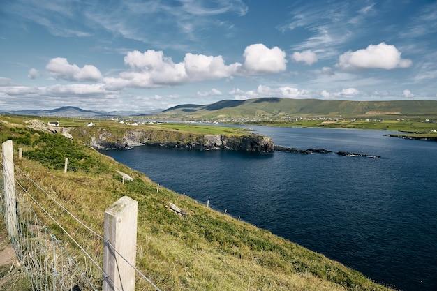Valentia island omgeven door de zee onder het zonlicht en een bewolkte hemel in ierland Gratis Foto