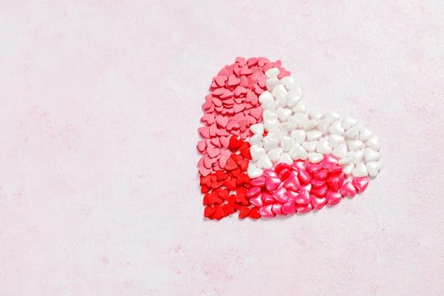 Valentijnsdag achtergrond, hartvormige snoepjes, hagelslag, bovenaanzicht Gratis Foto