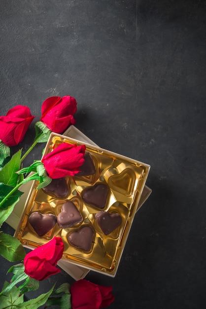 Valentijnsdag achtergrond met chocolade harten en rode rozen Premium Foto