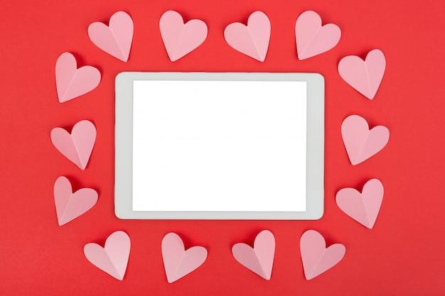 Valentijnsdag achtergrond met touchpad en papier harten. plat leggen. Premium Foto