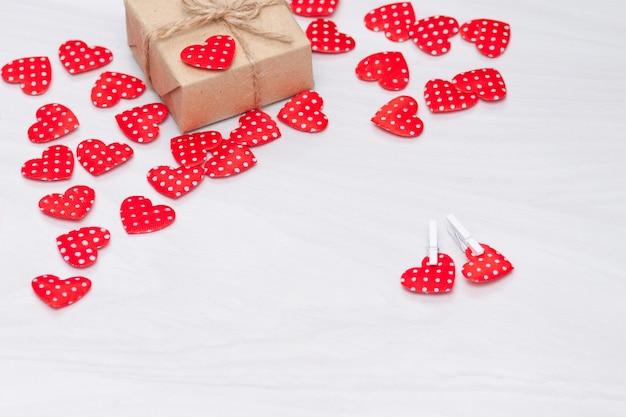 Valentijnsdag achtergrond. rode harten met geschenkdoos op witte houten achtergrond. valentijnsdag, liefde, bruiloft concept. plat lag, bovenaanzicht. Premium Foto