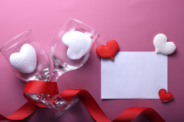 Valentijnsdag achtergrond wenskaart liefdesymbolen, rode decoratie met glazen op roze achtergrond. bovenaanzicht met kopie ruimte en tekst. plat leggen Premium Foto