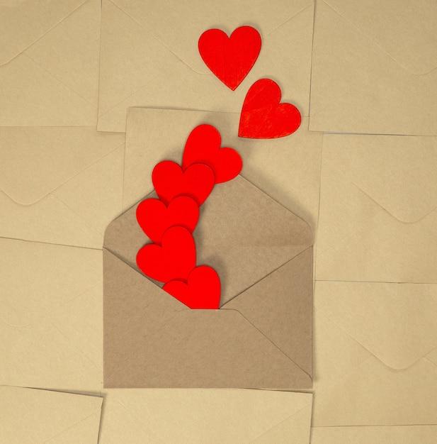 Valentijnsdag ambachtelijke envelop met rode harten op bruin gewoon papier achtergrond, romantische liefde ontwerp bovenaanzicht, kopie ruimte schoonheid Premium Foto