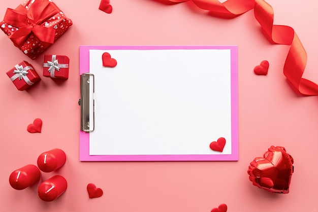 Valentijnsdag. blanco papier op roze klembord met valentijn decoraties kaarsen, ballonnen en confetti Premium Foto
