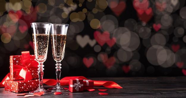 Valentijnsdag. champagne fluiten, kaarsen en rode harten op mooie bokeh achtergrond Premium Foto