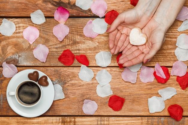 Valentijnsdag concept. vrouwelijke handen met hartjes op houten met bloemblaadjes en kopje koffie Gratis Foto