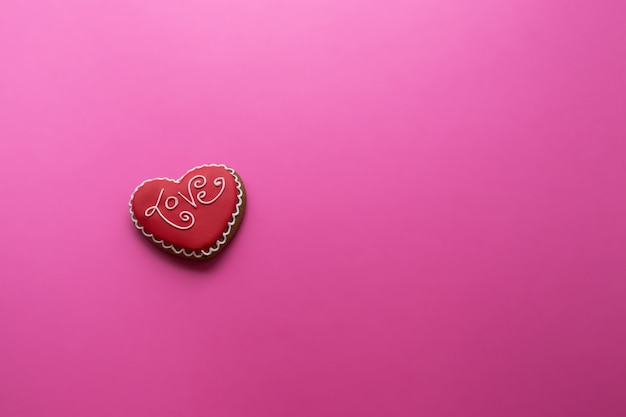 Valentijnsdag, een koekje met een opschriftliefde in de vorm van een hart op een roze, Premium Foto