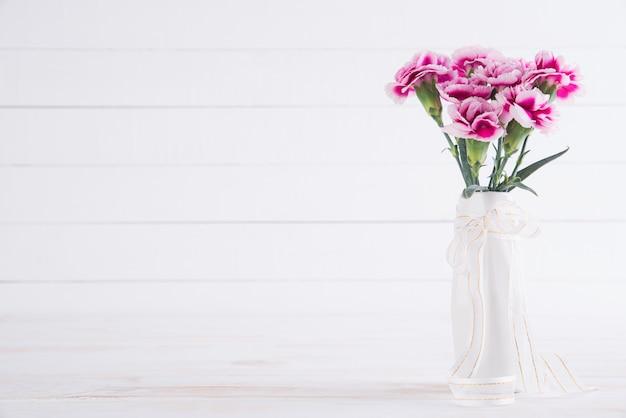 Valentijnsdag en liefde concept. roze anjerbloem in vaas op wit. Premium Foto