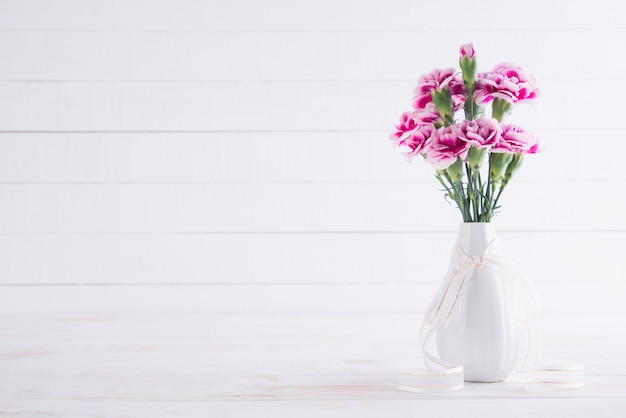 Valentijnsdag en liefde concept. roze anjerbloem in vaas Premium Foto