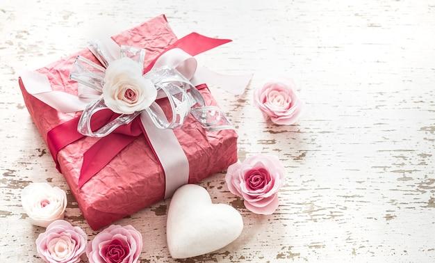 Valentijnsdag en moederdag concept, rode geschenkdoos met strik en rozen op lichte houten achtergrond Gratis Foto