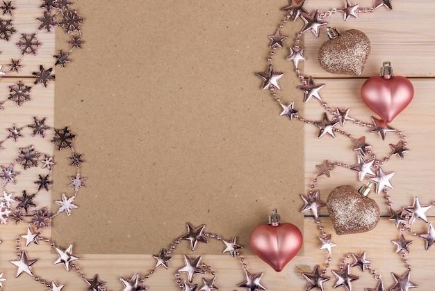Valentijnsdag frame samenstelling met roze harten, blanco vel papier op houten achtergrond. Premium Foto