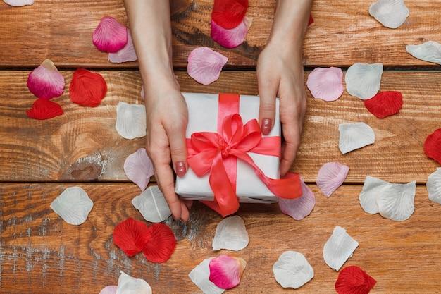 Valentijnsdag geschenk en vrouwelijke handen op houten met bloemblaadjes Gratis Foto