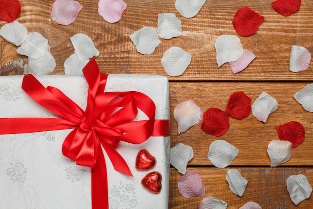 Valentijnsdag geschenk in witte doos en harten en bloemblaadjes op houten achtergrond Gratis Foto
