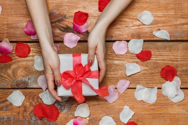 Valentijnsdag geschenk in witte doos en vrouwelijke handen en bloemblaadjes op houten achtergrond Gratis Foto