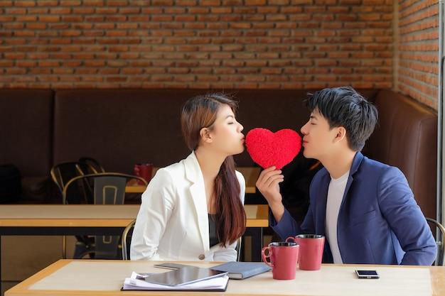 Valentijnsdag man gaf het rode hart aan een meisje om liefde te tonen. Premium Foto