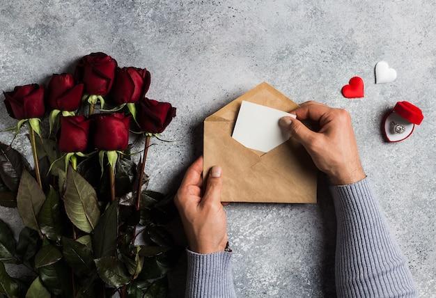 Valentijnsdag man hand met envelop liefdesbrief met wenskaart Gratis Foto
