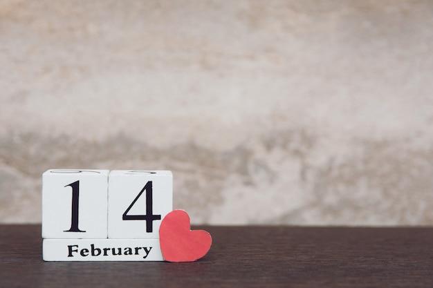 Valentijnsdag met 14 februari. houten witte blokkalender op houten lijstachtergrond met exemplaarruimte Premium Foto