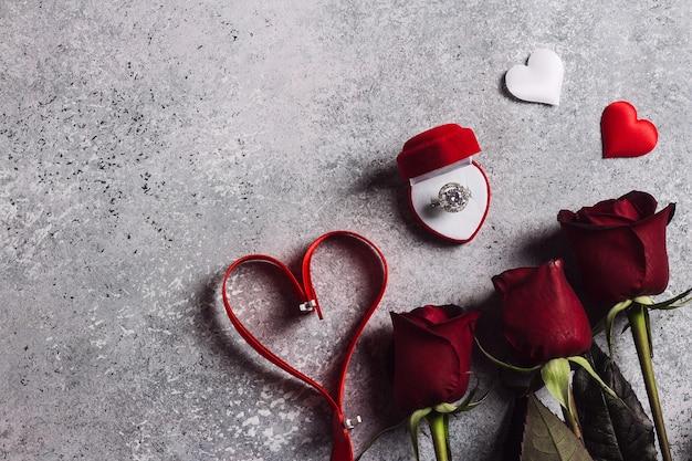 Valentijnsdag met me trouw verlovingsring in doos met rode rozen Gratis Foto