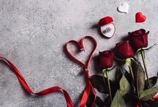 Valentijnsdag met me trouw verlovingsring in vak met rode rozen boeket en lint hart Gratis Foto