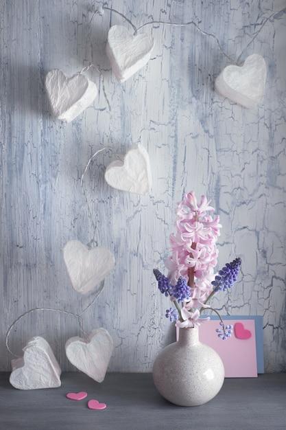 Valentijnsdag of lente viering, vaas met hyacint bloemen en garland lichten met papieren harten Premium Foto