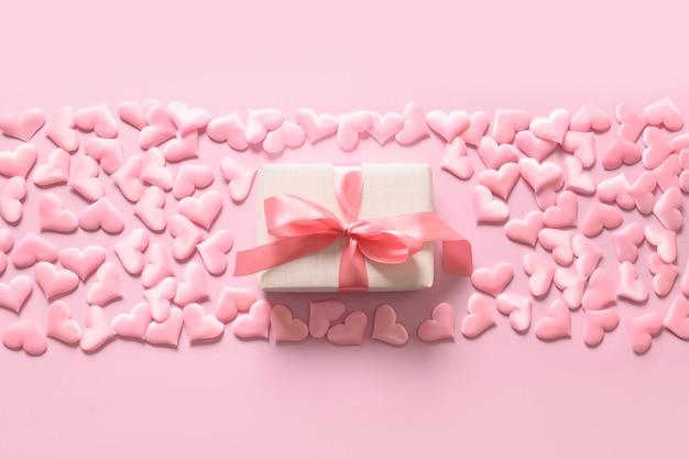Valentijnsdag of pasgeboren girly cadeau en harten op roze achtergrond. romantische wenskaart met kopie ruimte. Premium Foto