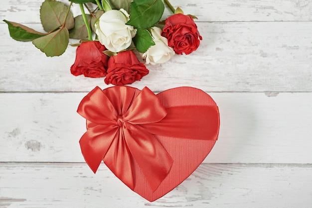 Valentijnsdag romantische decoratie met rode rozen en geschenkdoos. happy valentine's day wenskaart. Premium Foto