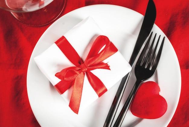 Valentijnsdag tabel instelling met plaat, vork, mes, geschenkdoos en rood hart, op rood tafellaken scène bovenaanzicht Premium Foto