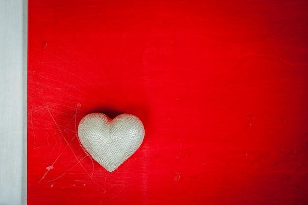 Valentijnsdag. trouwdag. zilveren hart op rode houten achtergrond. Premium Foto