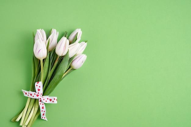 Valentijnsdag, verjaardag concept. wit tulpenboeket dat met hartenlint wordt verfraaid op groene achtergrond. ruimte kopiëren, bovenaanzicht Premium Foto