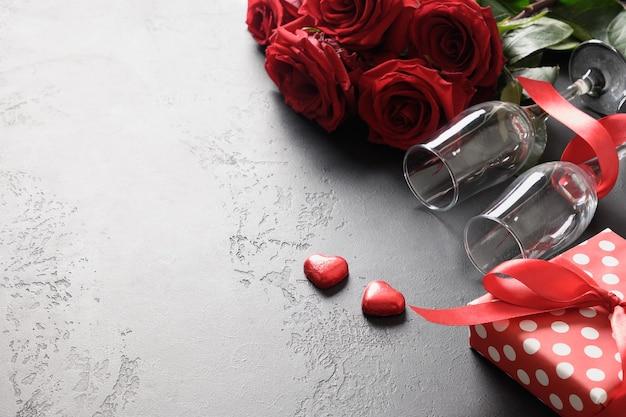 Valentijnsdag wenskaart met rode rozen, wijnglazen en cadeau op zwart met kopie ruimte. detailopname. Premium Foto
