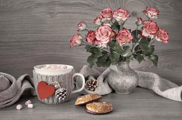 Valentijnsdagstilleven met kop warme chocolademelk met marshmallows, roze rozen en sjaal Premium Foto