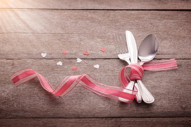 Valentijnskaartendag met tafelzilver en hart op houten wordt geplaatst dat Premium Foto