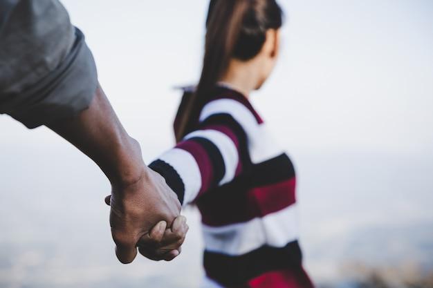 Valentijnsparen die hand in hand lopen, beloofden elkaar liefdevol te verzorgen Gratis Foto