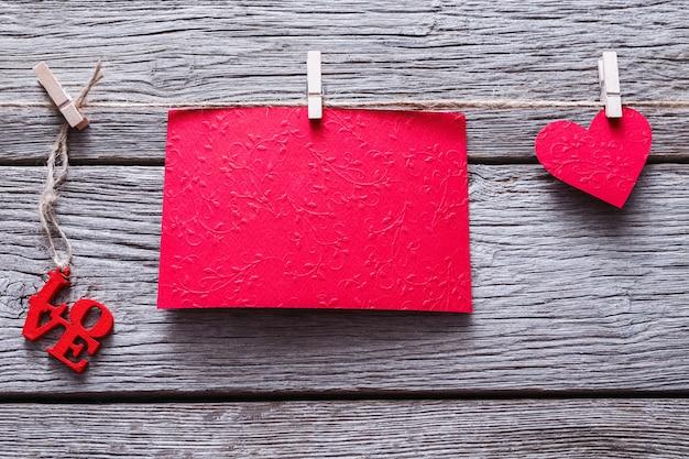 Valentine achtergrond met rood papier hart en lege wenskaart op wasknijpers op rustieke houten planken. happy lovers day card mockup, kopieer ruimte Premium Foto