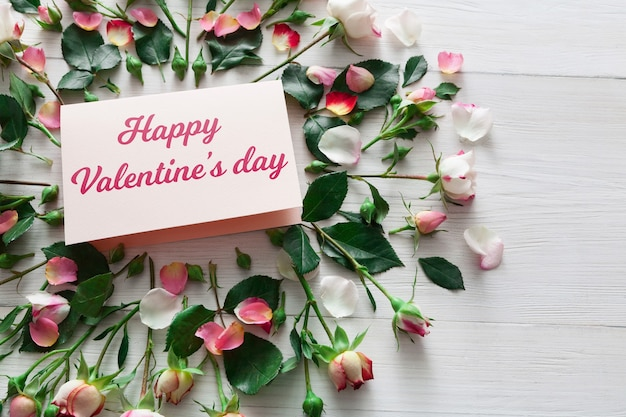 Valentine achtergrond met roze roze bloemen cirkel en handgeschept papier kaart met kopie ruimte op wit rustiek hout. mockup voor gelukkige geliefden Premium Foto