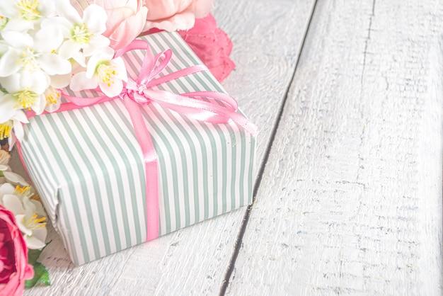 Valentine dag achtergrond met bloemen en verpakte geschenkdozen Premium Foto