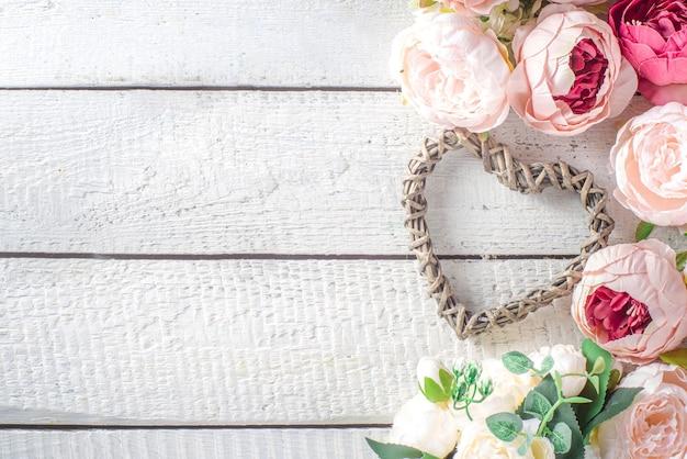 Valentine dag achtergrond met tedere roze rood witte pioenroos bloemen en hart Premium Foto