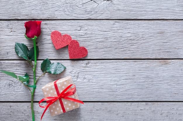 Valentine-dagachtergrond, handgemaakte harten en roze bloem op hout Premium Foto