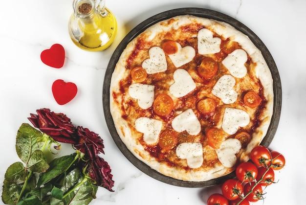 Valentine-vakantievoedsel, pizzamargarita met hartvormige kaas, wit marmer, copyspace hoogste mening, met rozen Premium Foto