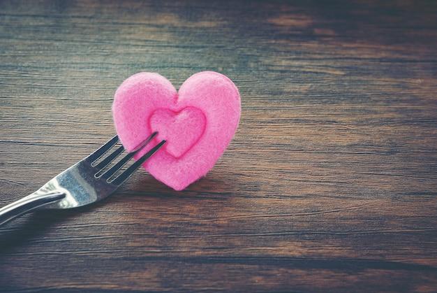 Valentines diner romantische liefde eten en liefde koken concept romantische tabel instellen versierd met vork en roze hart op houten Premium Foto