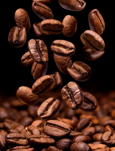 Vallende koffiebonen. donker met kopie ruimte Premium Foto
