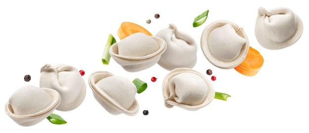 Vallende rauwe dumplings, bevroren zelfgemaakte russische pelmeni geïsoleerd op wit Premium Foto