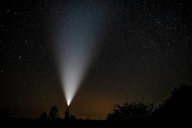 Vallende sterren gezien in de buurt van een zaklamp in handen van de mens Gratis Foto