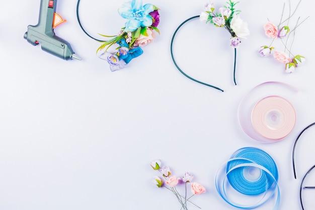 Valse kunstbloemen en linten voor het maken van haarband op een witte achtergrond Gratis Foto