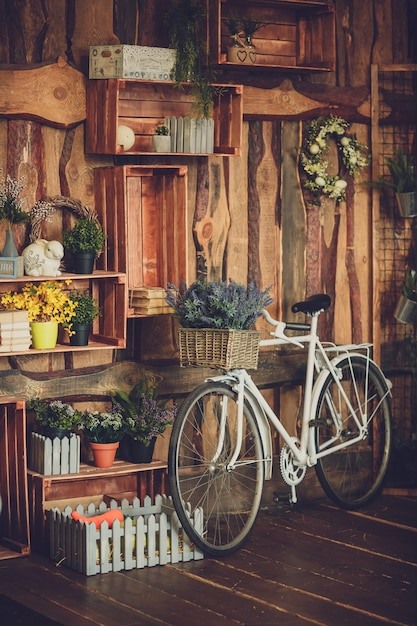 Valse plastic bloemen in mand op witte retro fiets Premium Foto