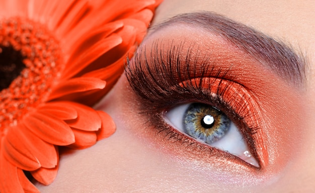 Valse wimpers en mode-oogmake-up met oranje bloem Gratis Foto